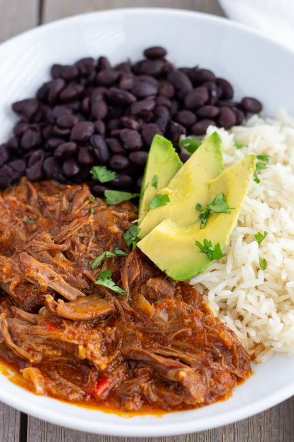 White bowl with Black beans, shredded meat in red sauce, white rice, and sliced avocado.