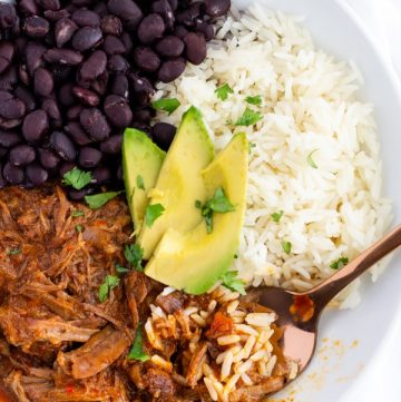 Overhead view of dish with Mexican Pot Roast, white rice, black beans, and topped with sliced avocado.