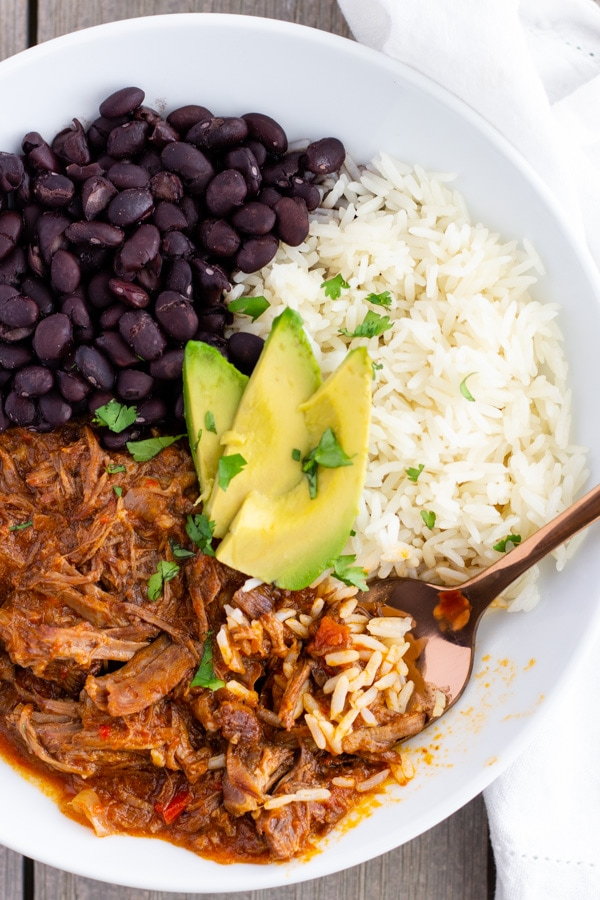 Overhead view of Mexican pot roast in a white bowl with white rice and black beans on the side and sliced avocado on top.
