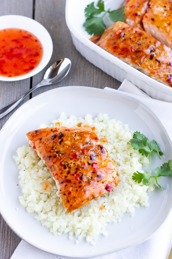 Overhead view of salmon on a plate of cauliflower rice with a side of sweet chili sauce and more salmon in a baking dish.