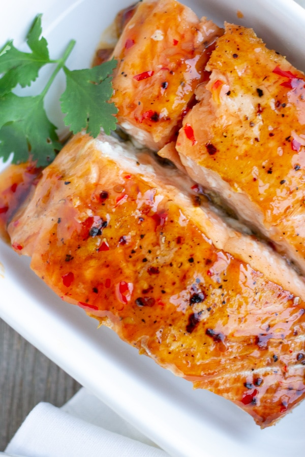 Up close view of 2 salmon fillets with sweet chili sauce in a white baking dish.