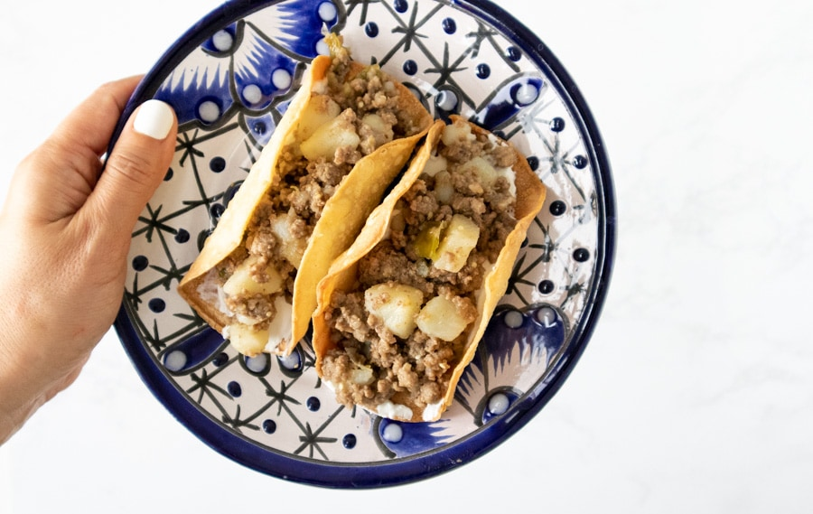 Hand holding plate with 2 tacos.