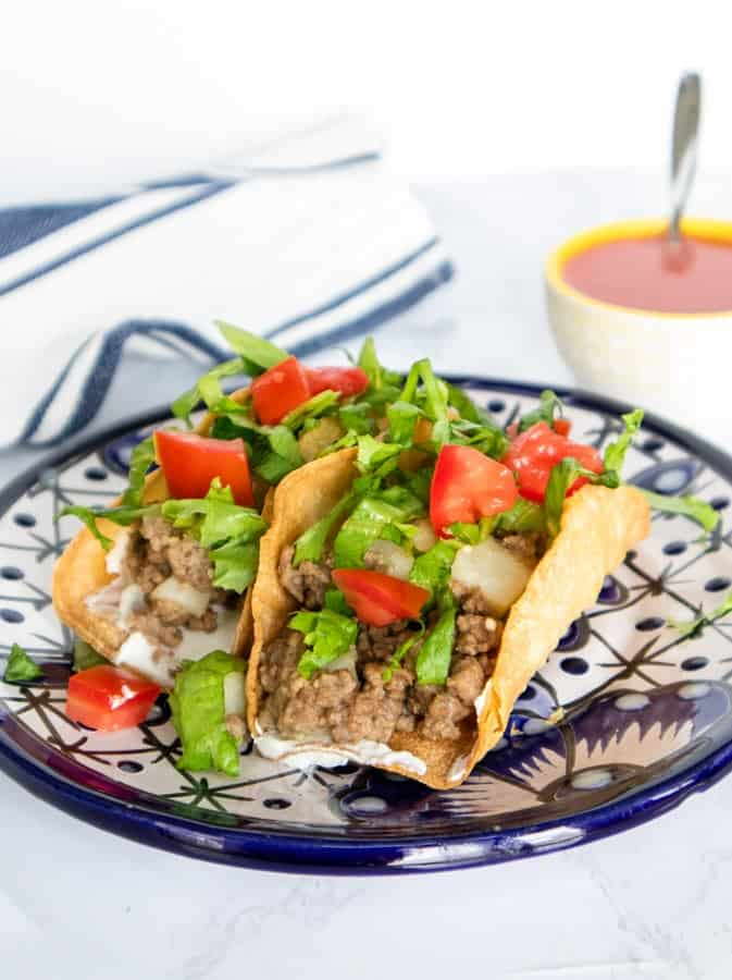Two crispy picadillo tacos on a blue plate.