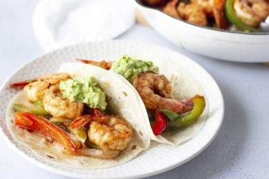 Two shrimp fajitas on a white plate.