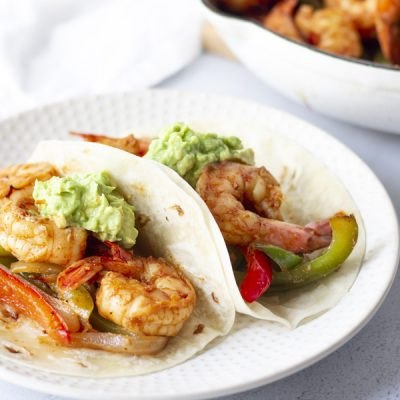 Two shrimp fajitas on a white plate.