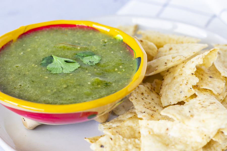 Salsa verde in a bowl on a plate with chips.