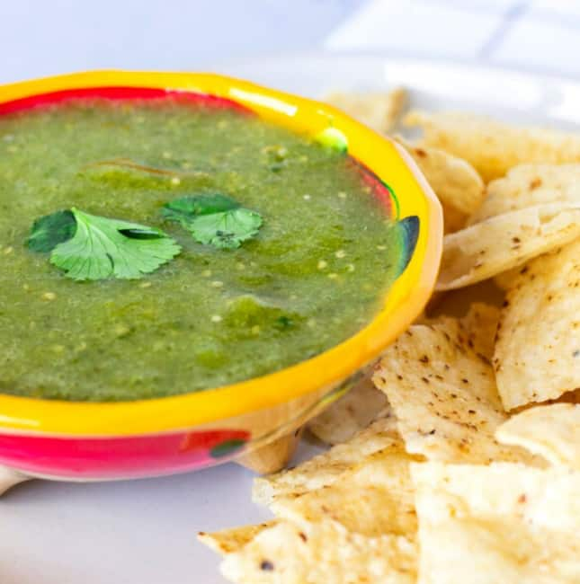 Up close view of salsa verde in a yellow bowl with tortilla chips on the side.