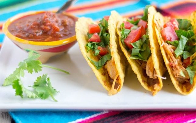3 tacos on a white plate under a colorful Mexican placemat.