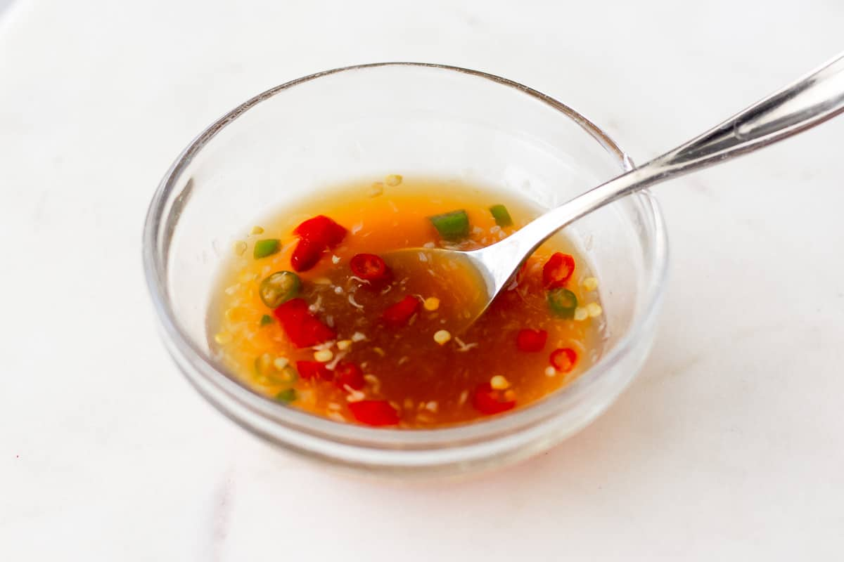 Spicy dressing in a small glass bowl.