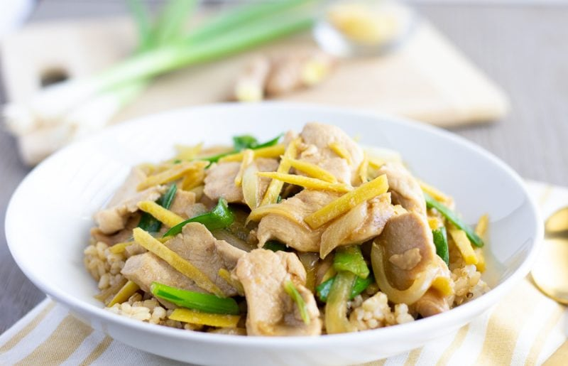 Thai Ginger stir fry in a white bowl served on top of rice.