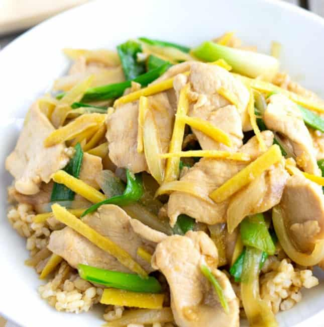 Up close view of stir fry with ginger, chicken and green onion slices.
