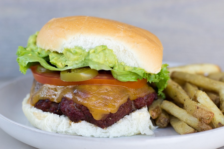 Chorizo Burger with Guacamole and french fries on the side.