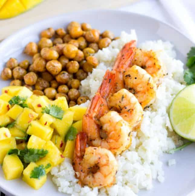 Shrimp lined up on a bed of rice with mango salsa and chickpeas.