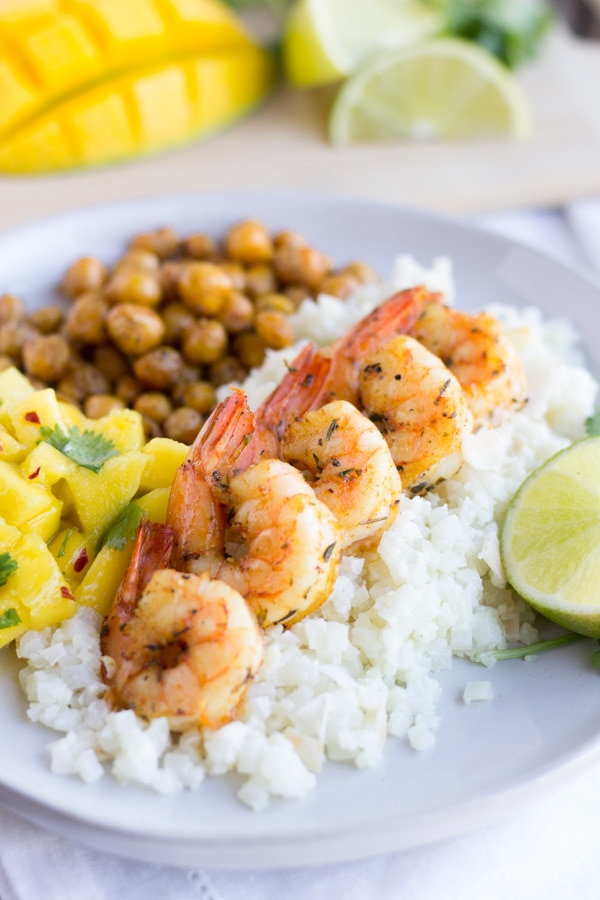 Jerk shrimp on top of rice with mango salsa and chickpeas on the side.