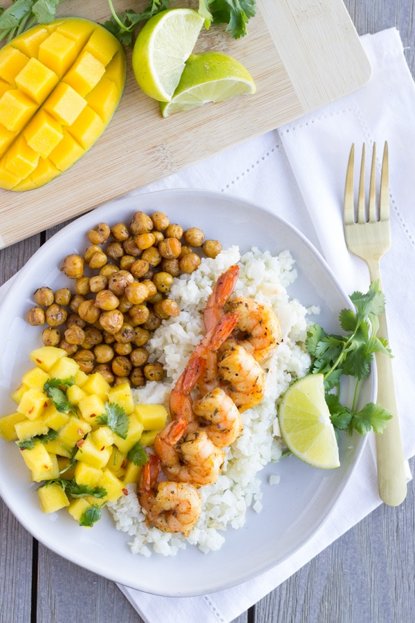 Overhead view of shrimp dish with a sliced mango on the side.