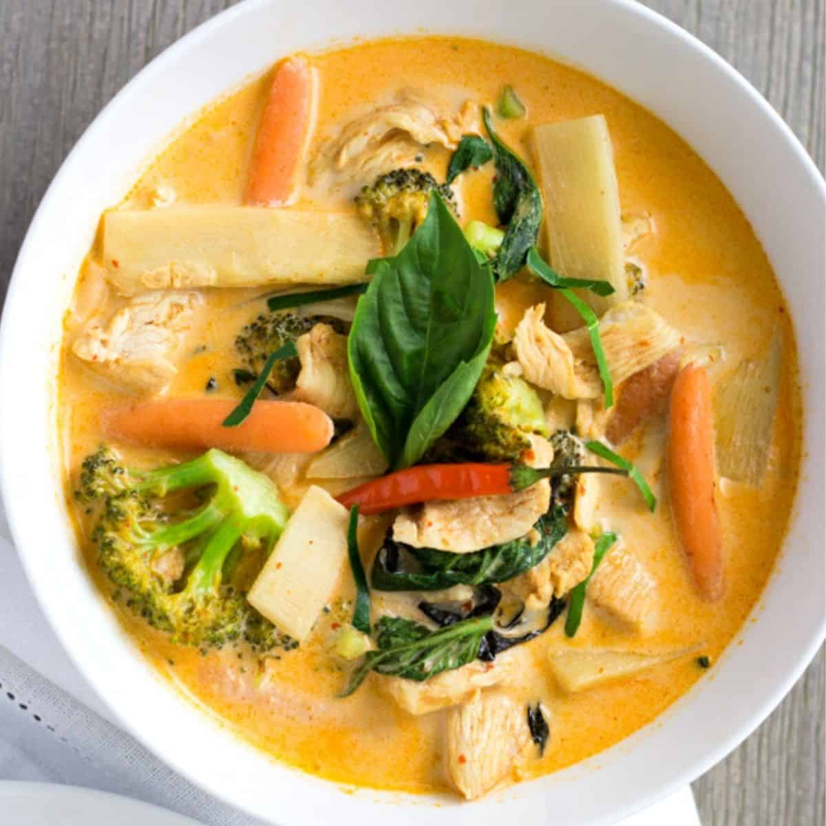 Overhead view of red curry in a white bowl with bamboo shoots, carrots, chicken, and broccoli.