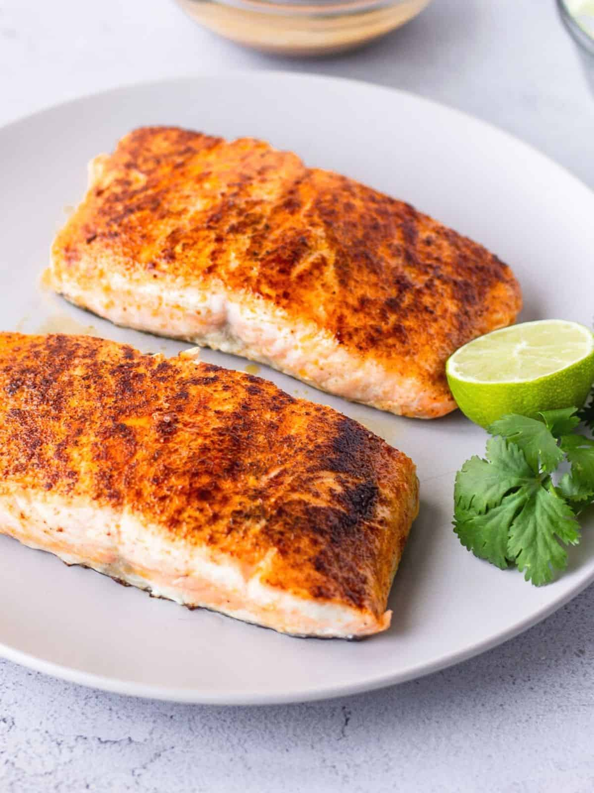Two pieces of cooked salmon filets on a white plate.