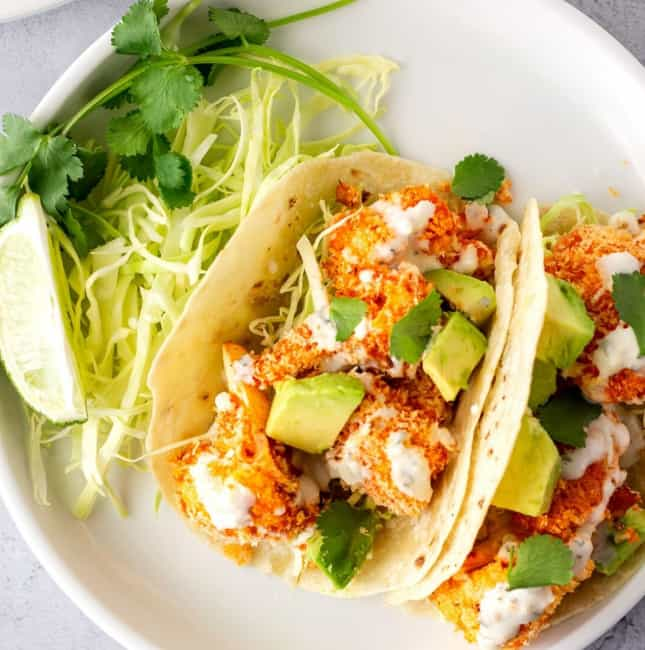 2 Tacos on a plate with a side of cabbage and cilantro.