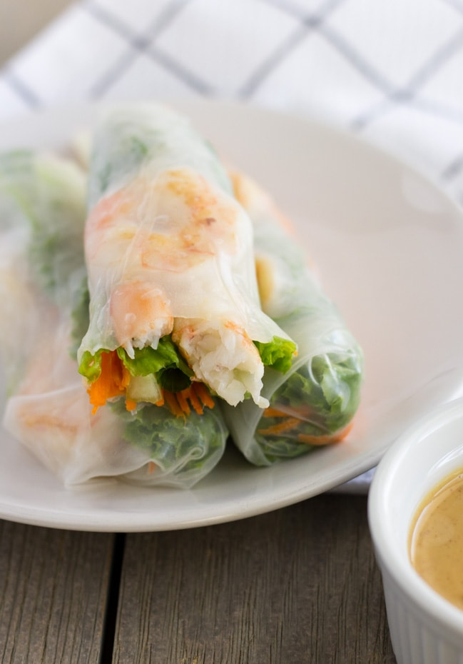Three rice paper rolls on a plate with a bite in the top one.