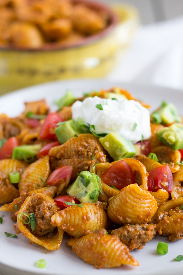 Up close view of small pasta shells, ground beef, diced avocado, tomato, and sour cream on top.