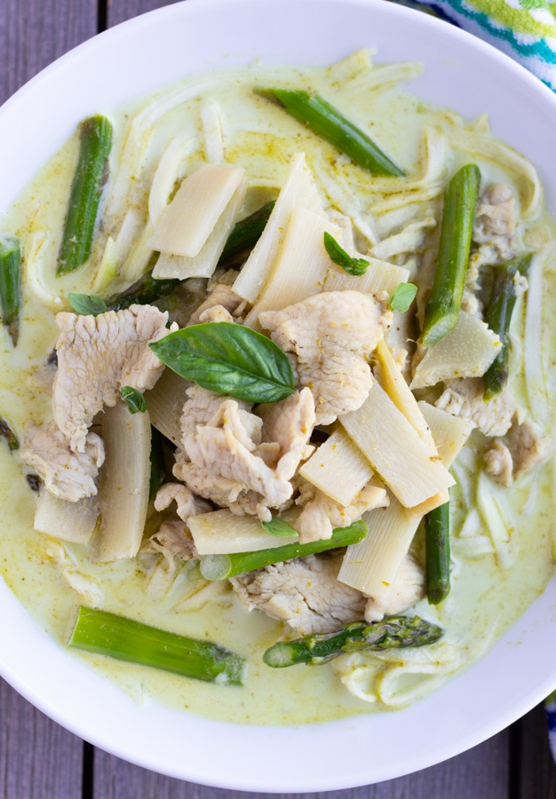 Overhead view of green curry in a white bowl with chicken, bamboo, asparagus, and zucchini noodles.
