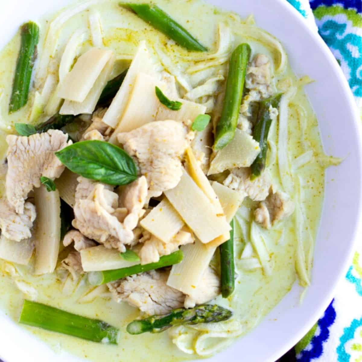 Feature image of green curry in a white bowl with chicken, bamboo, asparagus, and zucchini noodles.