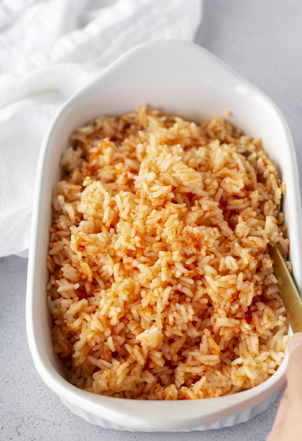 Rice in a white dish with a hand holding a gold spoon and white napkin on the side.