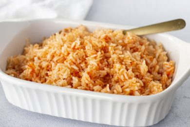 Rice in a white dish with a gold spoon and white napkin on the side.