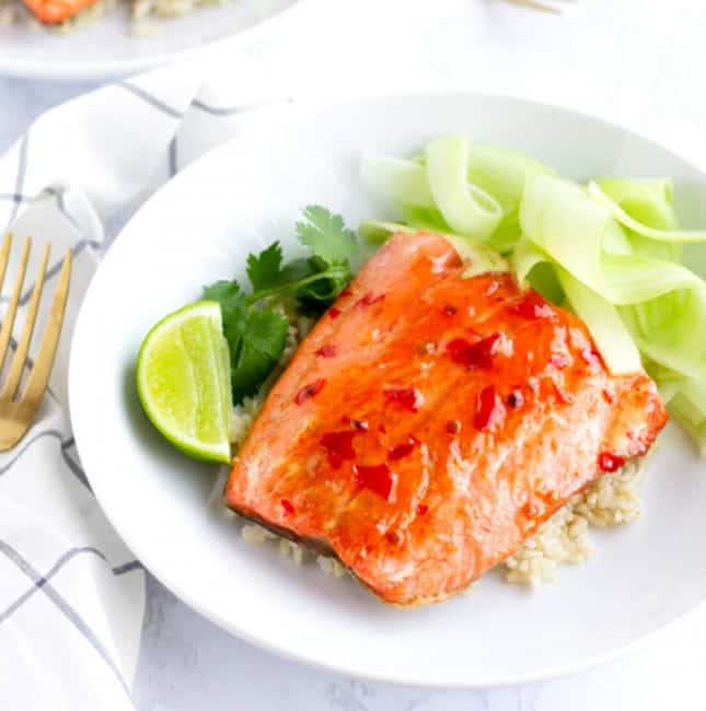 Chili Salmon on top of rice with ribbons of cucumber and a lime wedge.