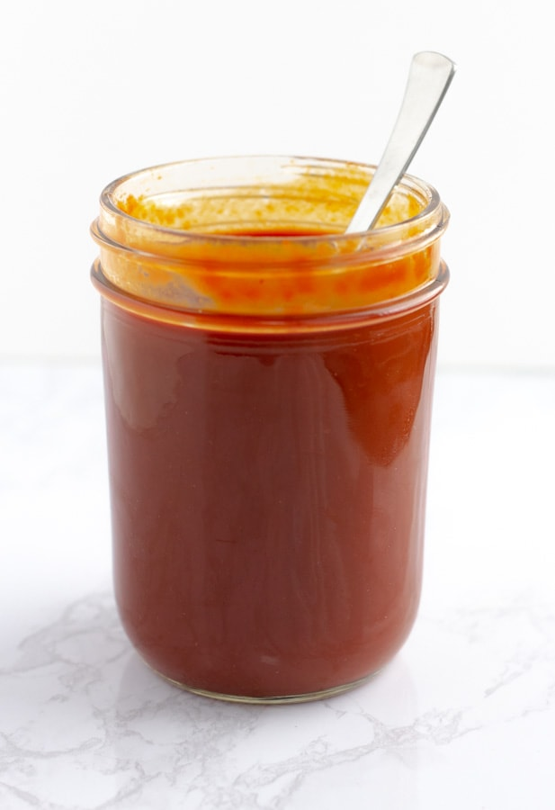 Red enchilada sauce in a glass mason jar.