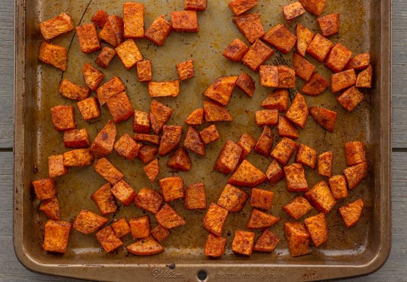 Sheet pan with baked diced sweet  potaotes.