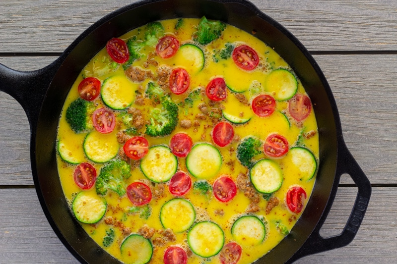 Unbaked frittata in a cast iron skillet.