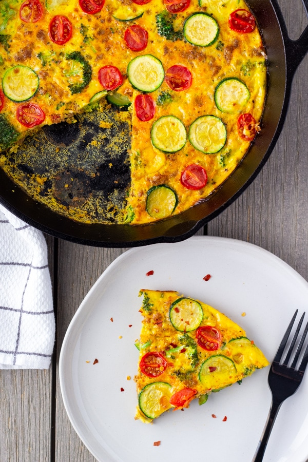 Slice of frittata on a plate with the whole one in a cast iron skillet on the side.