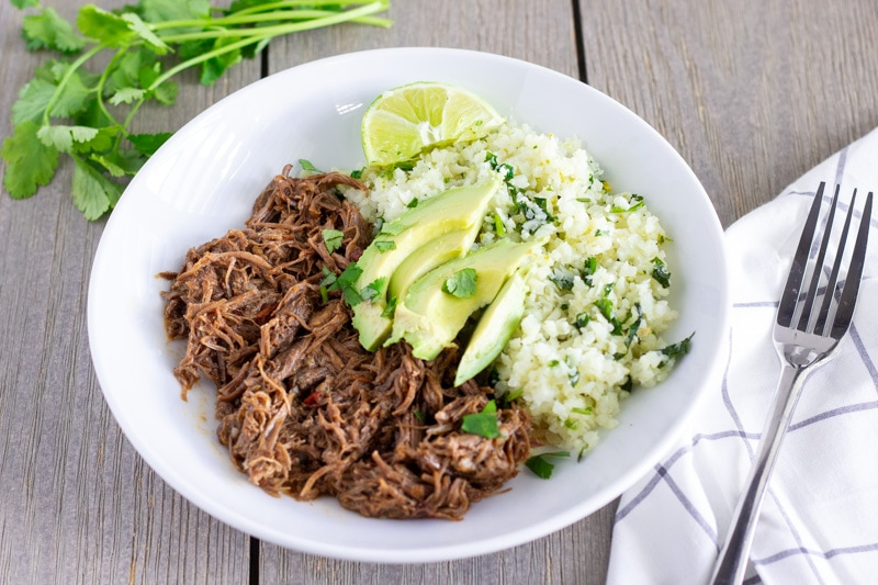 White bowl with shredded mexican beef, cilantro lime cauliflower rice, and topped with sliced avocado.