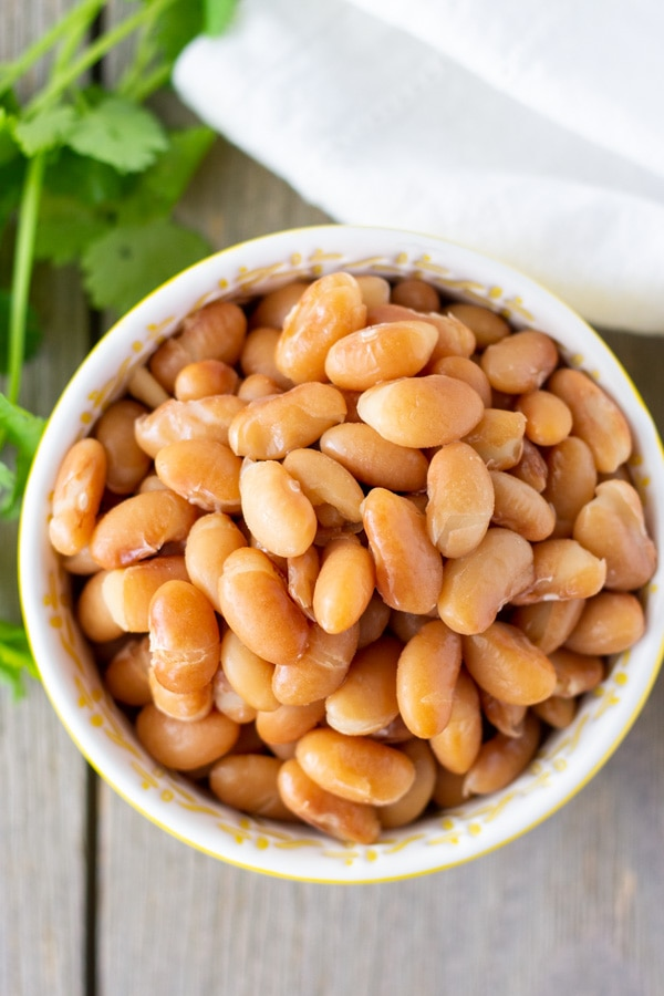 Overhead view of cooked whole beans in a small bowl with cilantro on the side.