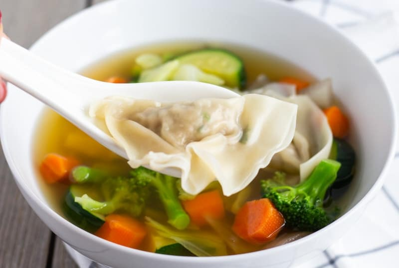 White Soup spoon holding one Wonton above soup with vegetables.