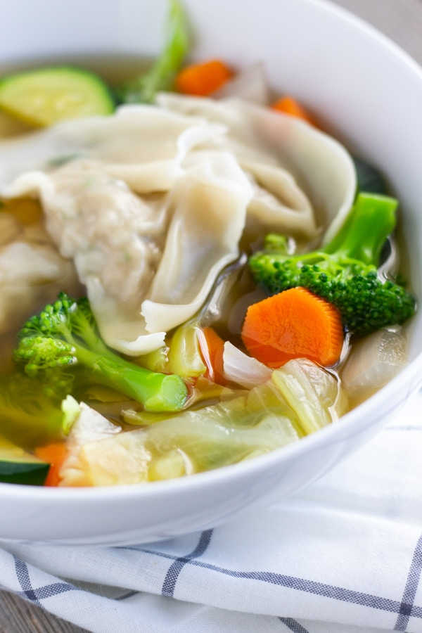 Angled view of Wonton and vegetable soup in a white bowl.