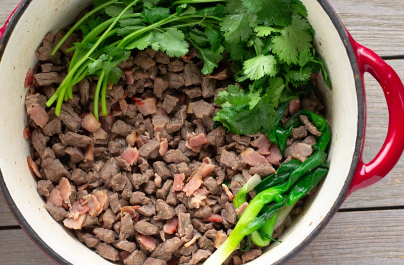 Dutch oven pot with beef, bacon, green onions and cilantro.