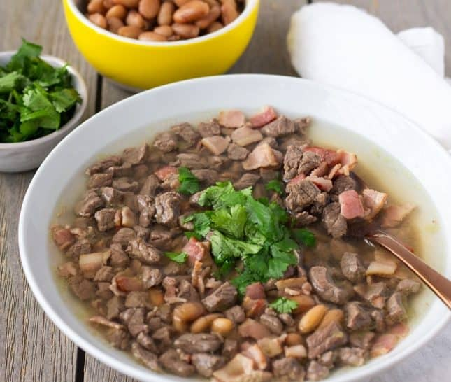 Carne en su jugo in a white bowl topped with cilantro and a bowl of beans on the side.