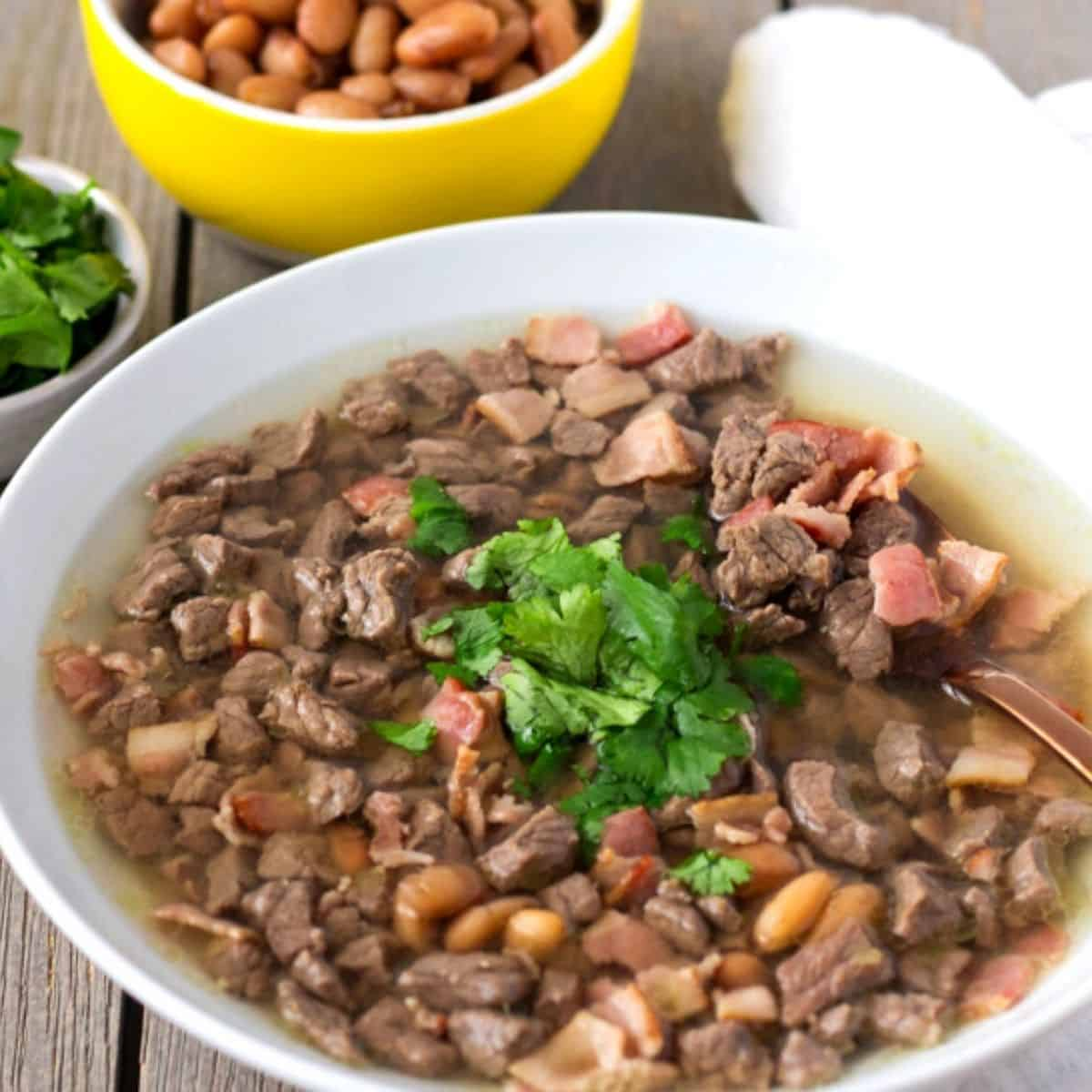 White bowl with broth, diced beef, whole beans, and cilantro garnish in the middle.