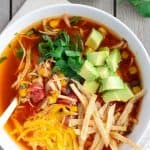 Overhead view of chicken tortilla soup in a white bowl with half an avocado and cilantro leaves on the side.
