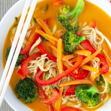Overhead view of Red Curry Noodles in a white bowl and chopsticks on the side.