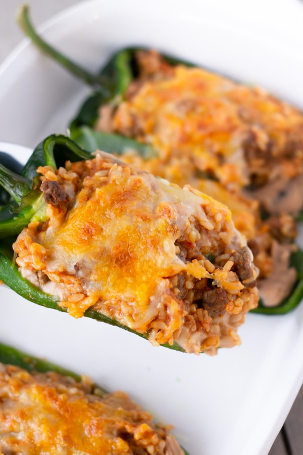 Cooked stuffed poblanos in a white baking dish with a close up of one being served.