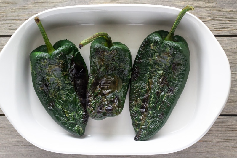 3 poblanos in a white ceramic dish after they have been blistered