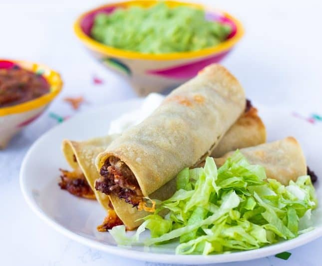 3 Taquitos on a white plate with shredded lettuce on the side. Small bowls of guacamole and red salsa on the side.