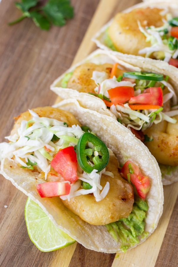 Fried shrimp tacos topped with slaw and jalapenos on a wood board.