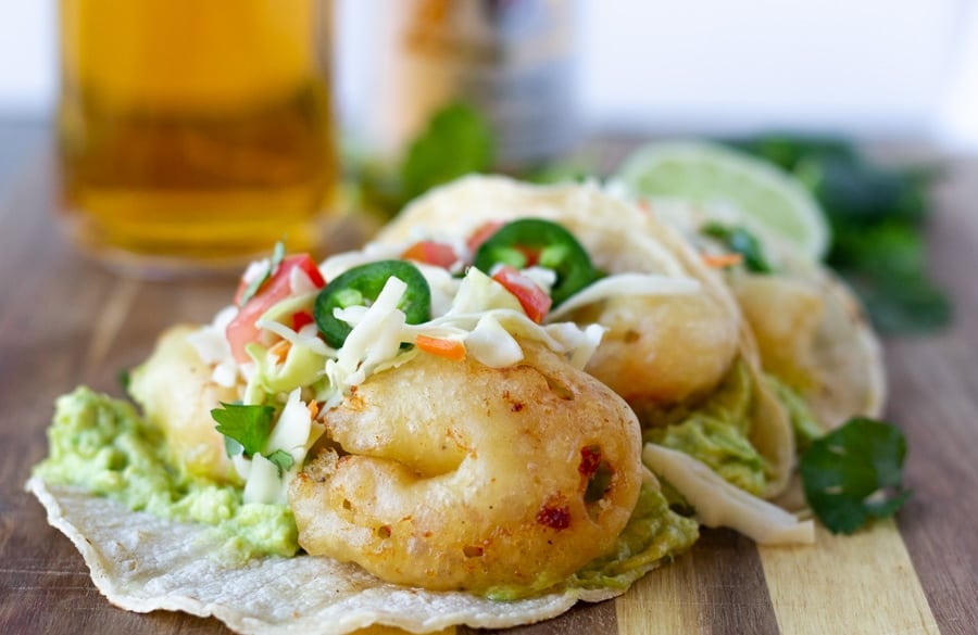 Beer Battered shrimp tacos topped with slaw and jalapenos on a wood board with a glass of Modelo on the side.
