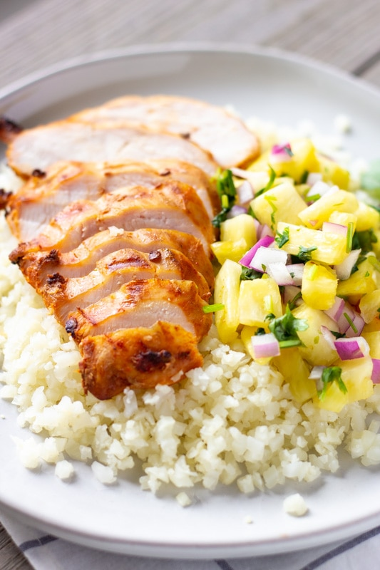 White plate with cauliflower rice on the bottom, sliced chipotle chicken on top and pineapple salsa on the side.