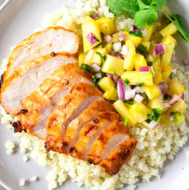 Sliced chicken on cauliflower rice with a side of pineapple salsa.
