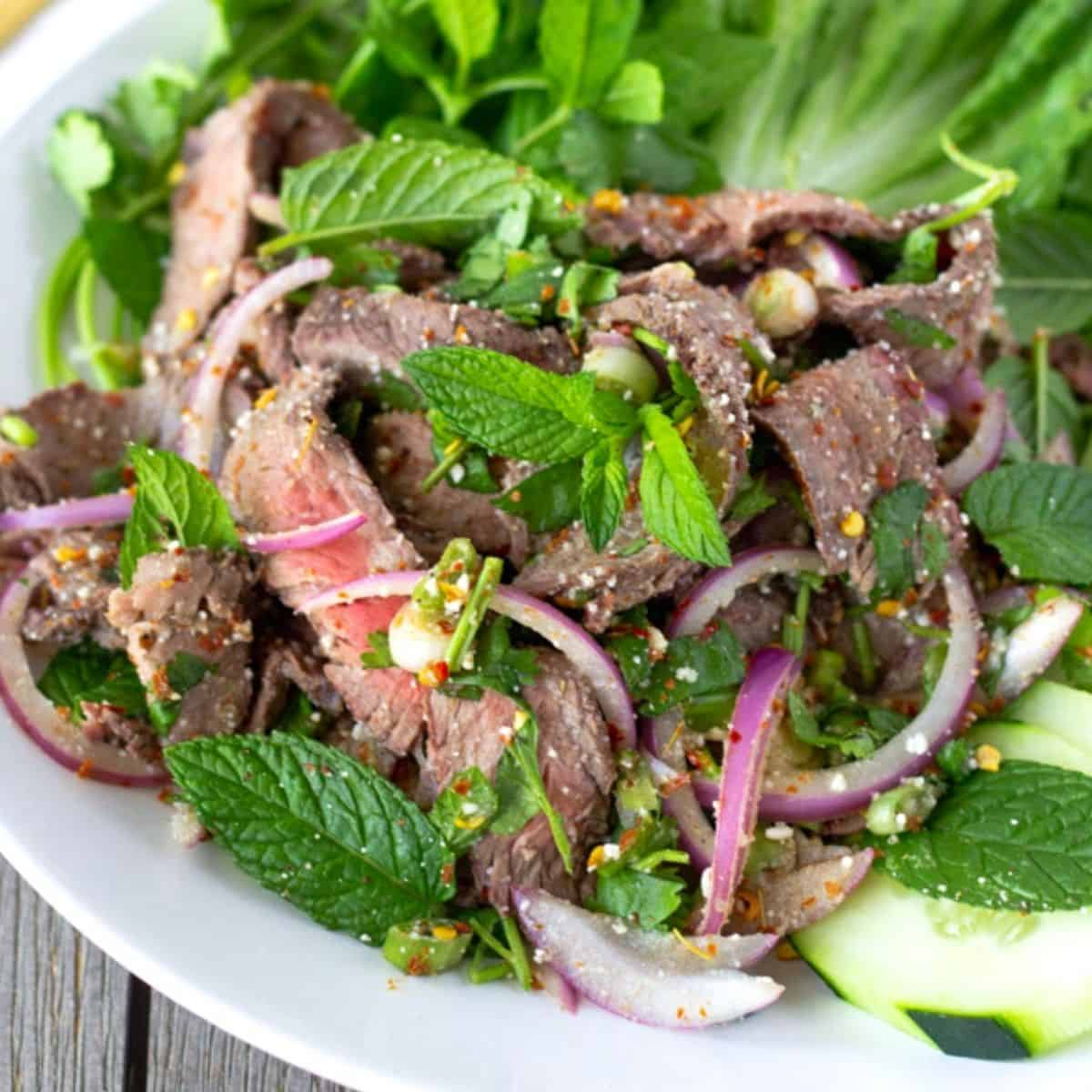 Up close view of sliced steak salad with mint, red onions, and a spicy Thai dressing.